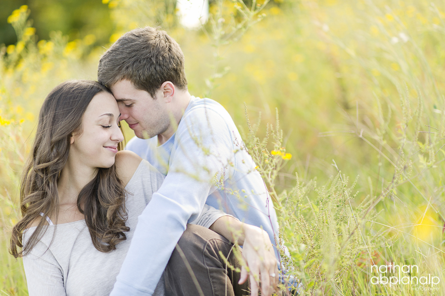 Couple touch foreheads in a field at Lake Norman in Charlotte NC