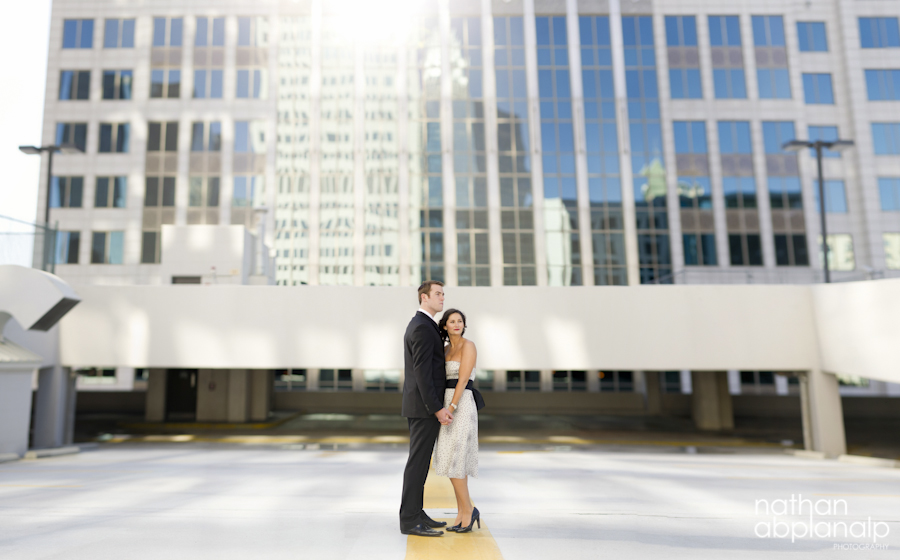 Couple embracing during an engagement session on a rooftop in uptown Charlotte NC