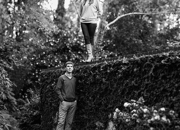 Woman standing on wall with finance during engagement photos in Myers Park Charlotte NC