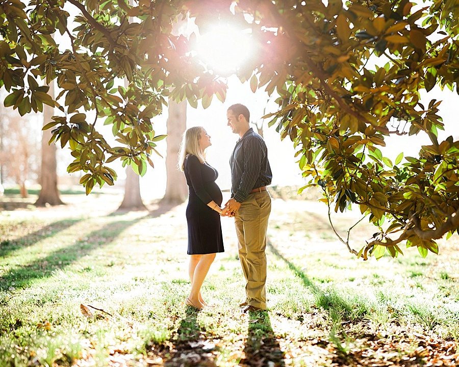 Husband and wife stand in the clearing of a magnolia tree at Independence Park in Charlotte NC