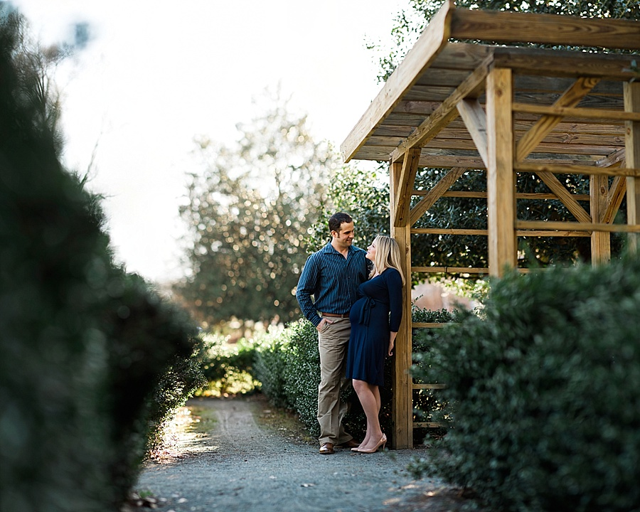 Husband and wife look at each other near the arbors at Independence Park in Charlotte NC