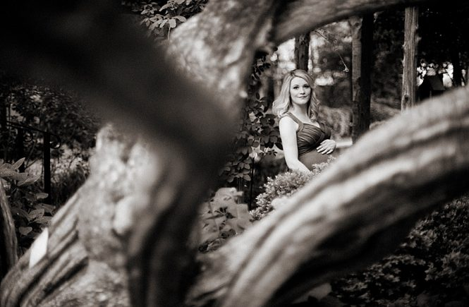 Expectant mother poses for maternity photos at Wing Haven Gardens in Charlotte NC