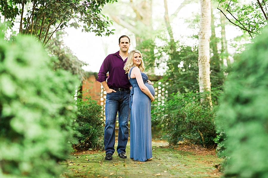 Man and woman stand together for maternity portraits at Wing Haven Gardens in Charlotte NC