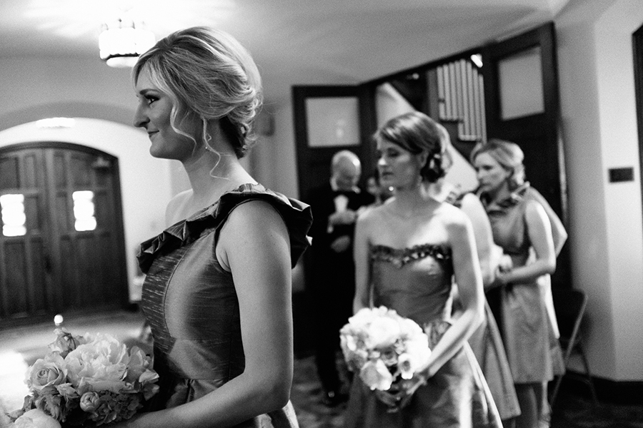 Bridesmaids look on as the bride dresses