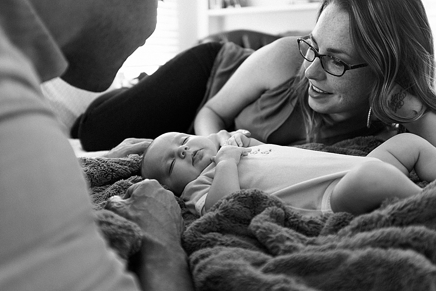 Mother and Father look on as their baby sleeps on bed in Charlotte NC