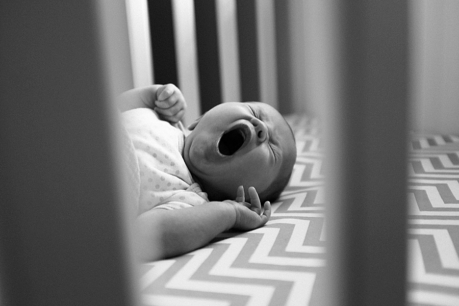 Baby yawns in crib with chevron sheets in Charlotte NC