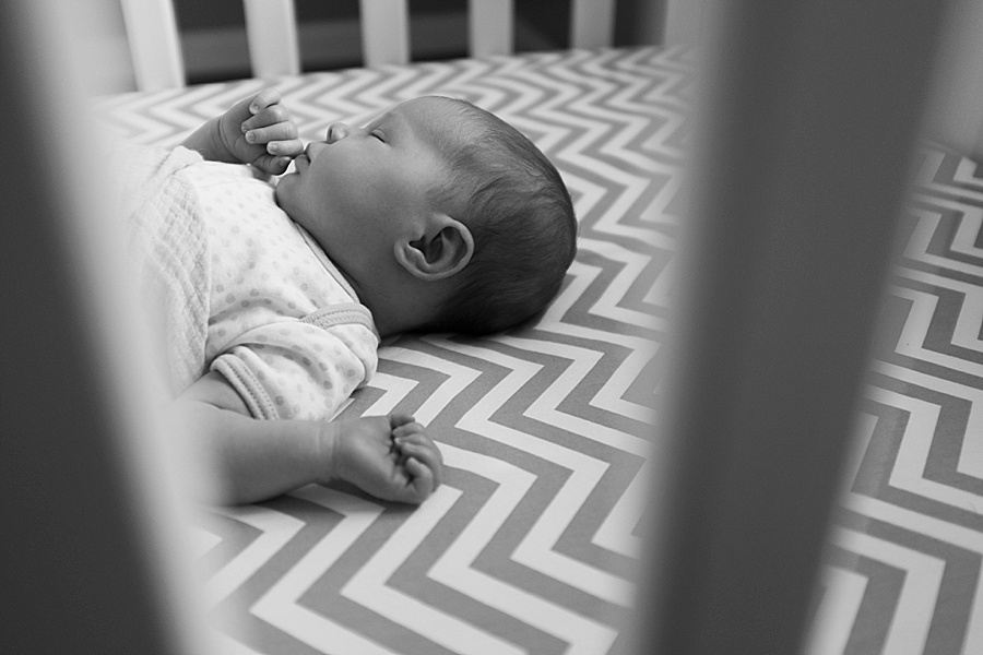 Newborn baby in crib with chevron sheets in Charlotte NC