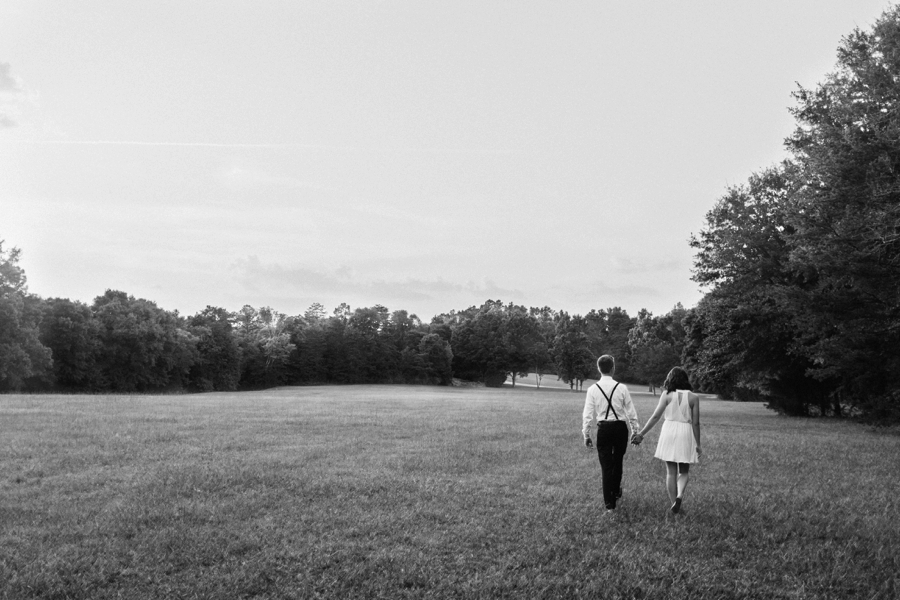 Couple walking hand in hand in field in Charlotte NC