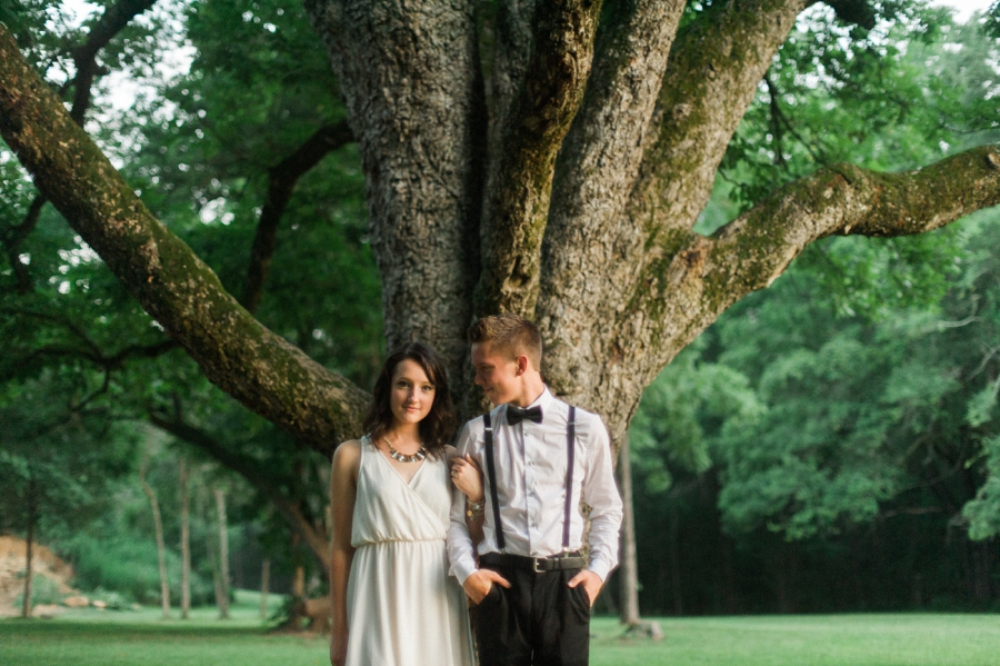 Future groom looks at his bride in front of large tree in Charlotte NC