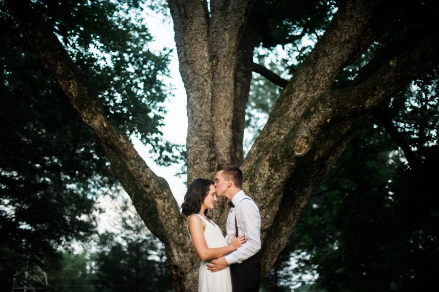 Man and woman embrace in front of large tree in Charlotte NC