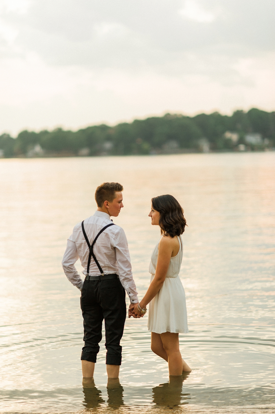 Couple holding hands on the shores of Lake Wylie in Charlotte NC