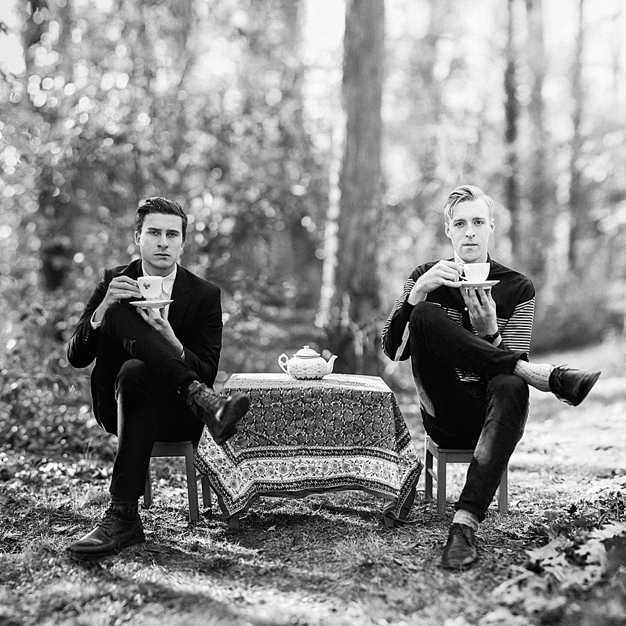 Two men sitting in little chairs sipping tea for The Cookie Cult in Charlotte NC