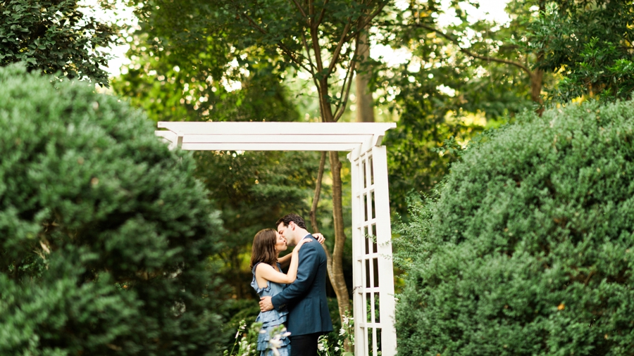 Couple hugging under arbor at Wing Haven Gardens in Charlotte NC