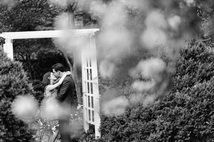 B&W of couple standing under arbor at Wing Haven Gardens in Charlotte NC